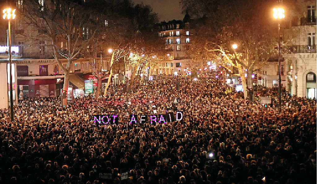 DEFIANCE SYMBOL: People gather in Paris to pay respect to those murdered at Charlie Hebdo.