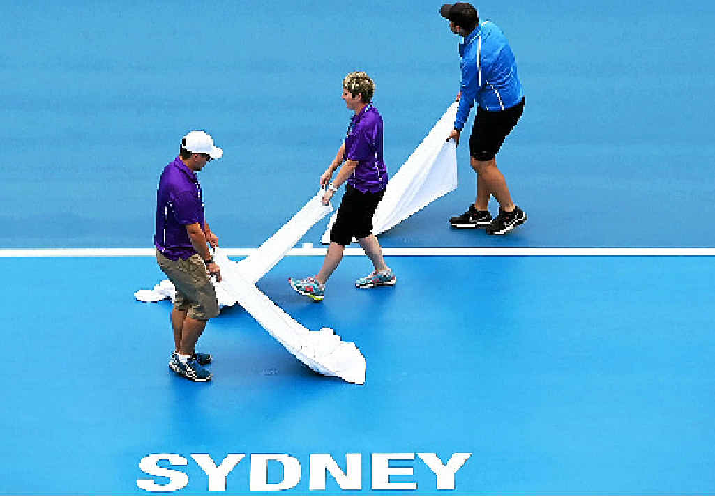 MOPPING UP: Ground staff dry the courts after persistent rain during the day one of the 2015 Sydney International.