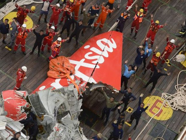 Members of the salvage crew with the tail section of the AirAsia jet liner, doomed flight QZ8501