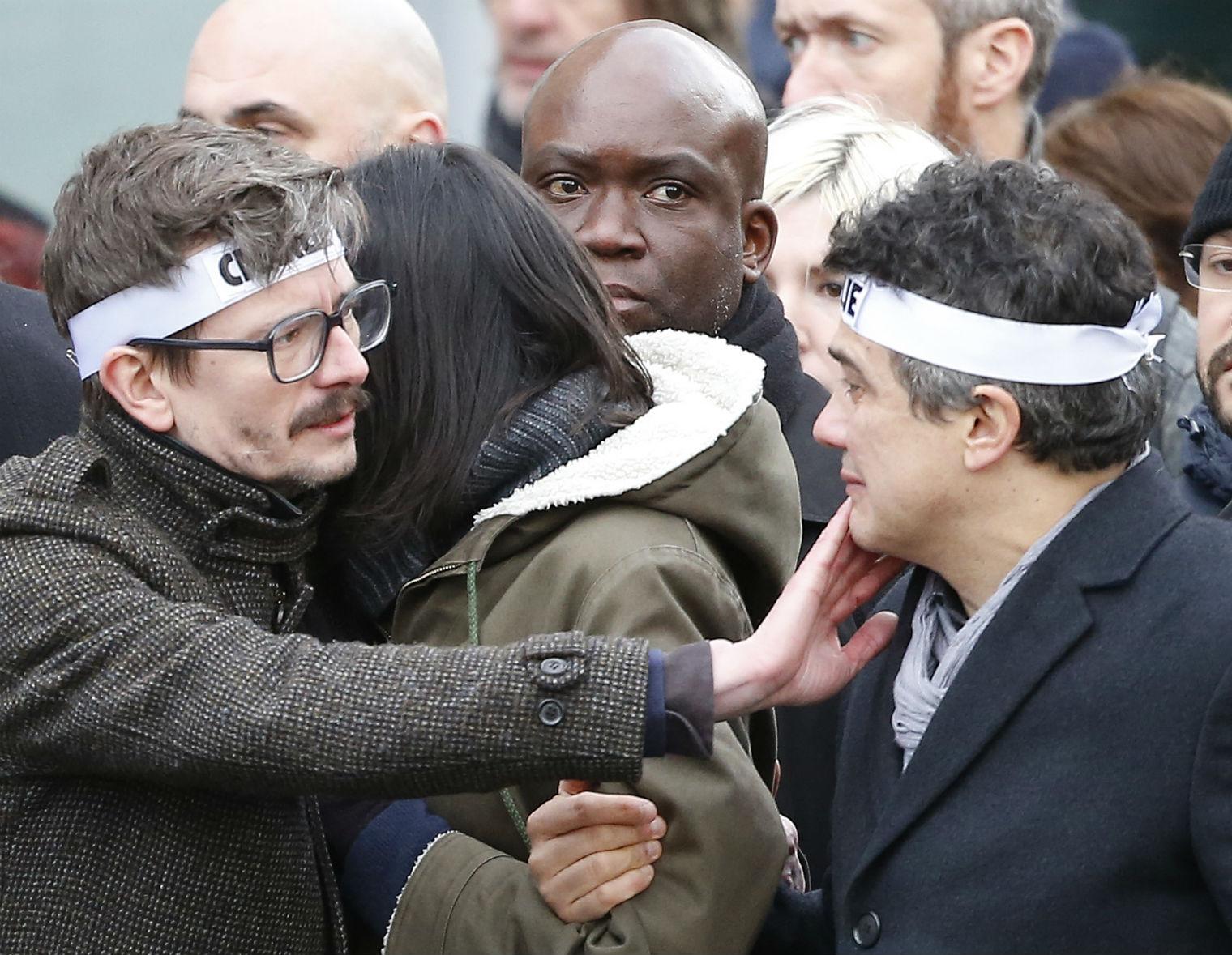 Charlie Hebdo cartoonist Luz comforts colleague, writer Patrick Pelloux.