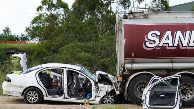 STUPIDITY: Police inspect a vehicle that recently crashed into the back of a truck on Redbank Plains Road at Blackstone after evading police.