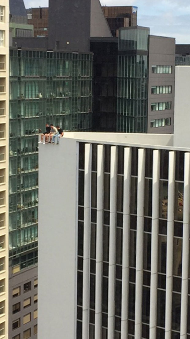 Don't look down: The young men dangle their feet over Auckland's West Plaza Building