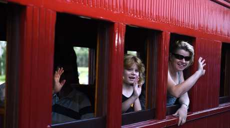 Passengers on the steam train wave to people on the platform as it arrives at Maryborough West station.