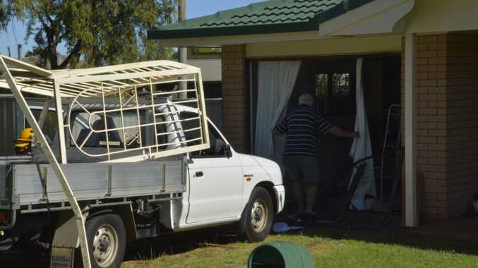 A man inspects damage to a Blaxland St home after a ute crashed through the front of it.