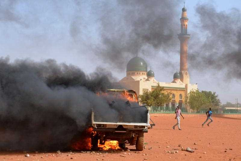 People run past a police truck Aset on fire by protesters during a demonstration against French weekly Charlie Hebdo's publication of a cartoon of the Prophet Mohammed in front of the grand mosque in Niamey on January 17, 2015.