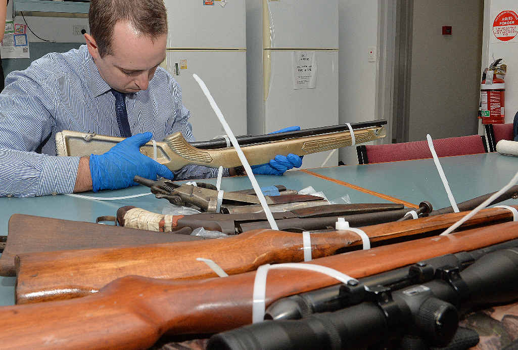 Plain clothes officer Senior Constable Kiel Duggen inspects some of the firearms seized in the raid at Andergrove.