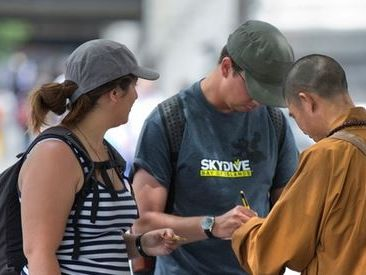 Two pedestrians in New Zealand being targeted by a fake monk - believed to be a member of an international syndicate.