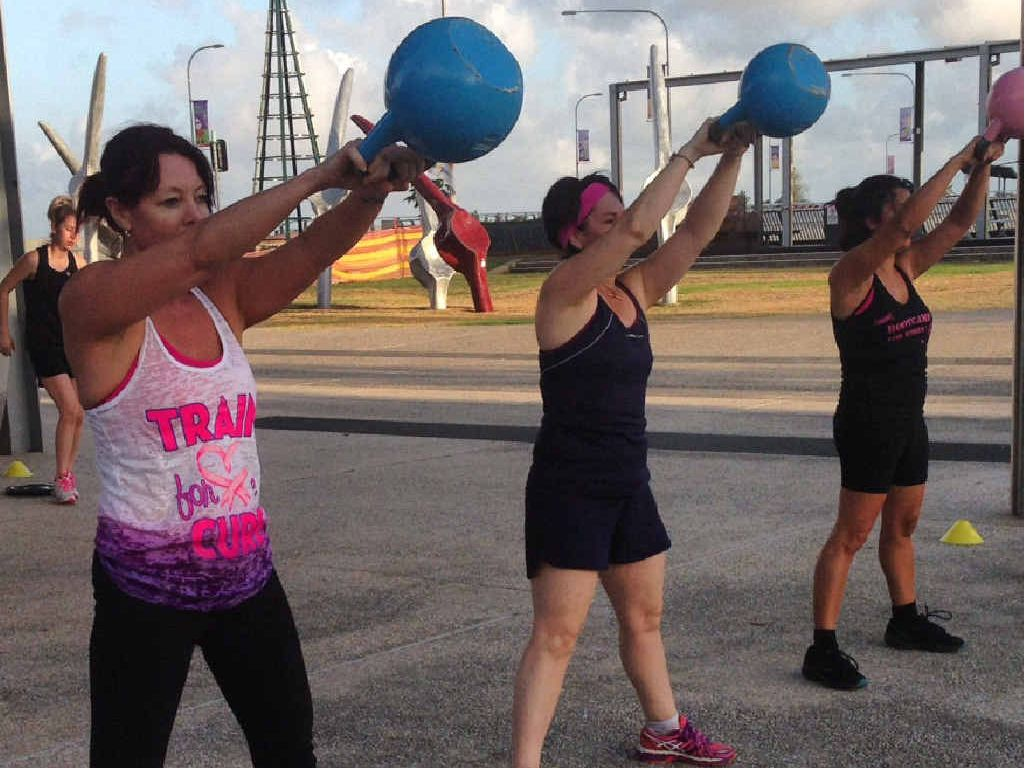 Richelle Underhill, Andrea Aitken and Dorianne Vassallo doing a kettlebell exercise during a RED E Personal Training boot camp.
