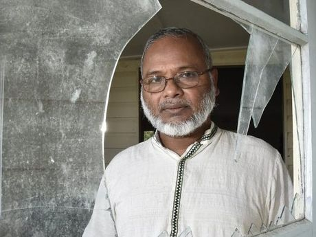 MOSQUE FIRE: Professor Shahjahan Khan looks over the smashed glass of the hall door believed to be the entry point for vandals who started the fire in the hall which is part of the Toowoomba Mosque complex, on West Street.