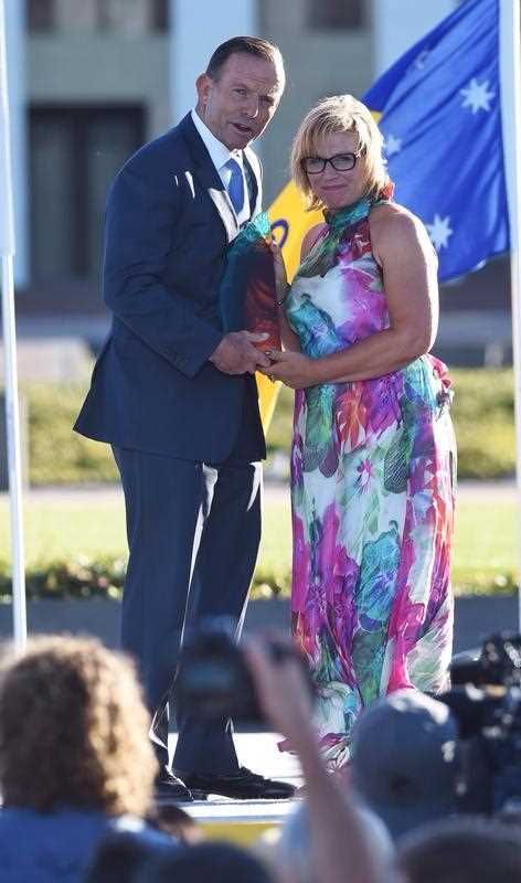 Prime Minister Tony Abbott presents Rosie Batty as 2015 Australian of the Year award at the Australian of the Year Awards at Parliament House lawns in Canberra, Sunday, Jan. 25, 2015.