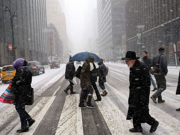 People battling across the city streets in New York; the city's mayor has warned that Juno could bring one of the biggest blizzards in history