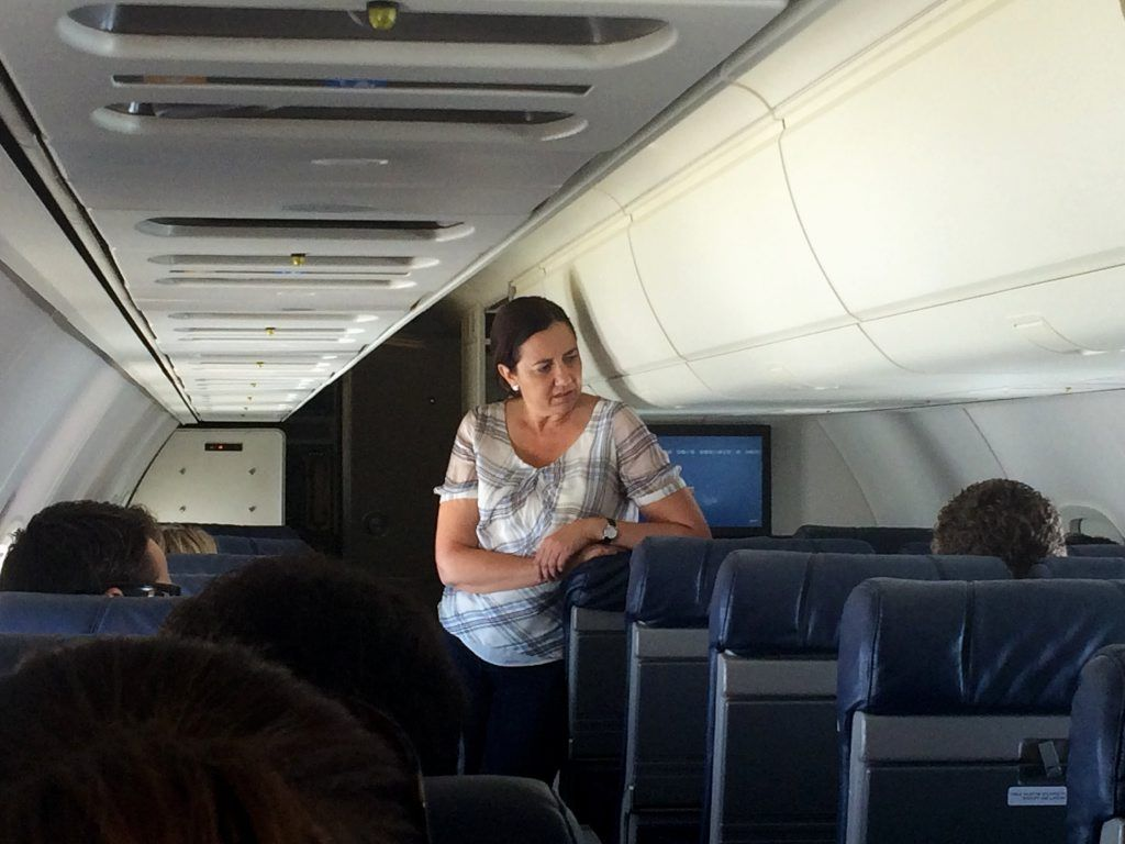 Annastacia Palaszczuk talks to her team during a flight.