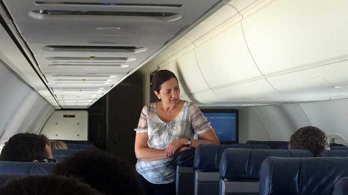 Annastacia Palaszczuk talks to her team during a flight.