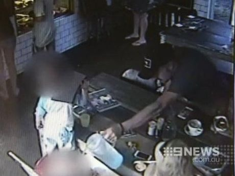 Jason Deller pours a jug of water over his child at a cafe. Image: Nine News