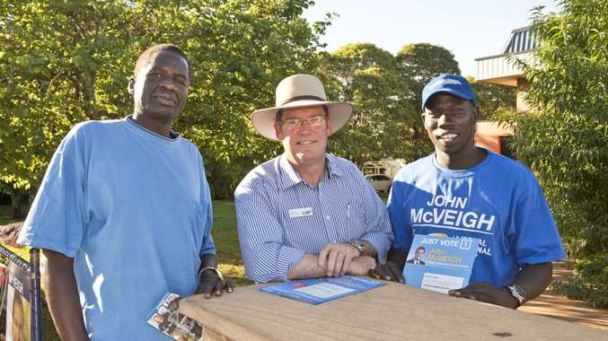 SAFE SEAT: Handing out how to vote cards at the Harristown State High School polling booth are (from left) Anyuon Liai, Member for Toowoomba North John McVeigh and Akoc Mathok. Saturday, Jan 31, 2015 . Photo Nev Madsen / The Chronicle