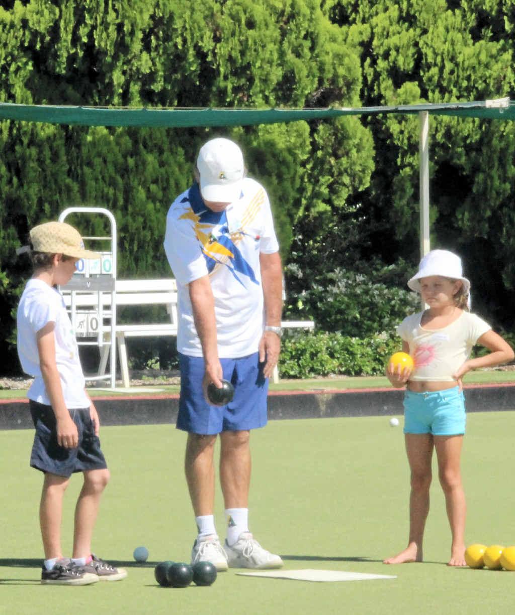 BOWLS FUN: Club coach Pete Stephan teaches young bowlers Simon Dwyer and Georgina Drysdale some new tricks.