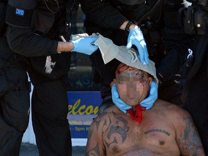 Members of the Dunedin armed offenders squad provide first aid to a man in Princes St, Dunedin, yesterday afternoon. Photo / ODT