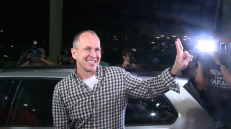 Peter Greste poses for photographers outside Brisbane International Airport.