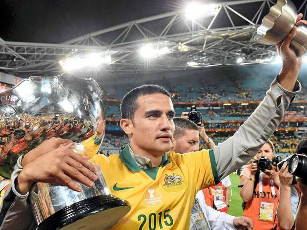 HEADING EAST: Tim Cahill celebrates with the Asian Cup last week.