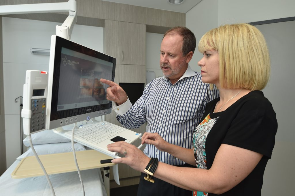 Uniting Care Health executive director Richard Royle gives Health Informatics Society chief executive Louise Schaper a run-down on some of St Stephens Hospital Hervey Bay's e-technology.