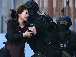 DAY THAT SHOCKED THE NATION: A panicked hostage runs to tactical response officers after escaping from the Lindt Cafe in Martin Place, Sydney.