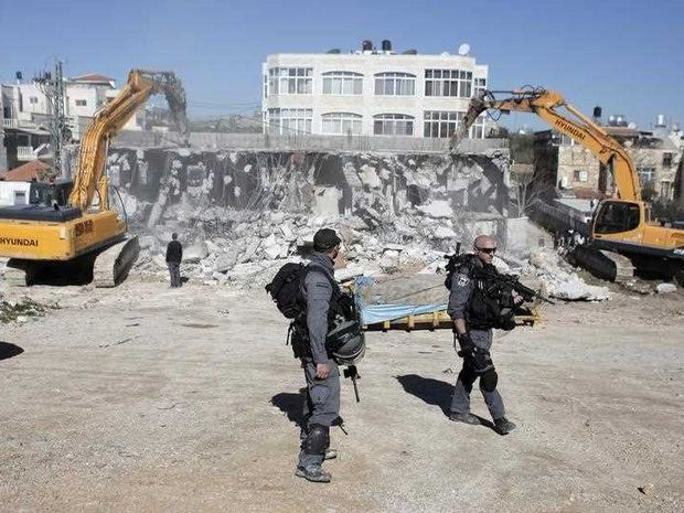 Members of the Israeli security forces stand guard as bulldozers hired by the Jerusalem municipality destroy a Palestinian house in the Israeli annexed East Jerusalem neighbourhood of Shuafat on January 21, 2015, on the grounds that it was built without a construction permit. Palestinian homes built without a construction permit are often demolished by order of the Jerusalem municipality.