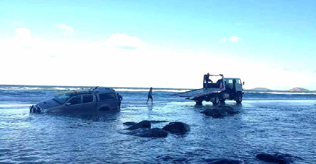 STUCK: The driver of this Toyota Hilux dual cab was winched off the Mudlo Rocks on Sunday afternoon in the first recovery mission at the infamous beach obstacle this year.
