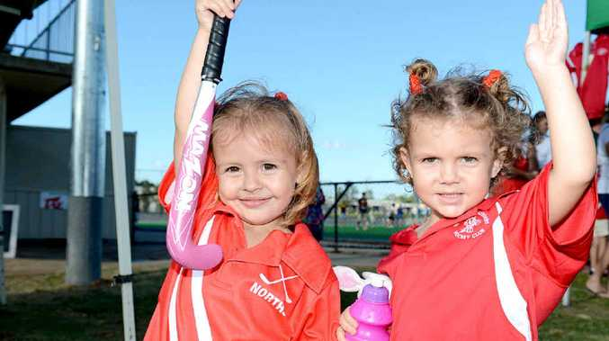KEEN TO PLAY: Three-year-old twins Madelaine (left) and Annaliese Bow-Lynch put their hands up to play for Norths during Sunday's Ipswich Hockey Open Day at Raceview.