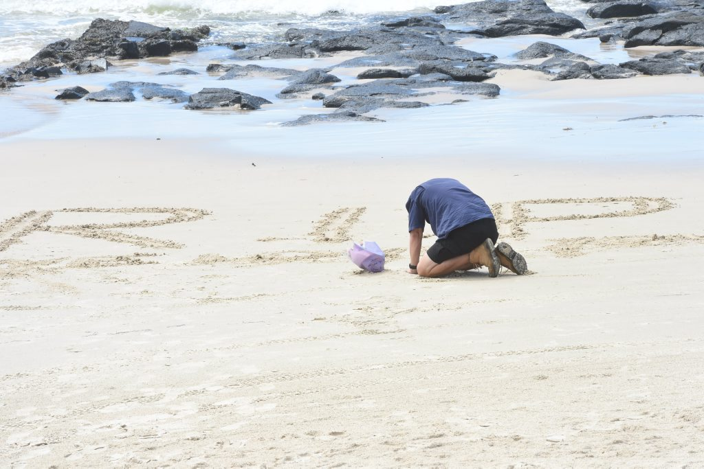 RIP TADASHI NAKAHARA: Neil Fitzgerald, of the Gold Coast, mourns the loss of his mate. The surfer died after being attacked by a shark at Shelly Beach, Ballina, on Monday morning. People have been visiting the site of the attack, to leave flowers and other memorials (above right) to the popular Japanese national.
