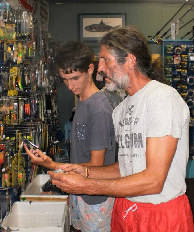 WHAT A CHOICE: Nymboida's John Cooper with son Shea spend the major prize of $500 worth of Daiwa tackle at Big River Bait and Tackle, Maclean as the winner of the 2014 Daily Examiner Fish of the Year Competition.PHOTO: DICK RICHARDS