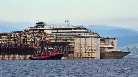 The refloated wreck of the Costa Concordia cruise ship as it was dragged to the harbor of Pra di Voltri near Genoa