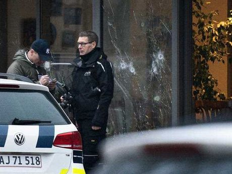 The scene outside the Copenhagen cafe, with bullet marked window, where a gunman opened fire Saturday, Feb. 14, 2015, in what is seen as a likely terror attack against a free speech event organized by an artist who had caricatured the Prophet Muhammad.