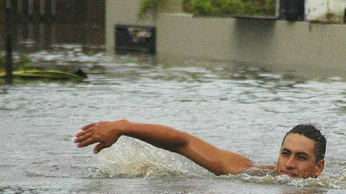 Richard Scrimshaw finds the appropriate way to get around at Perkins Street, North Mackay during the 2008 floods.