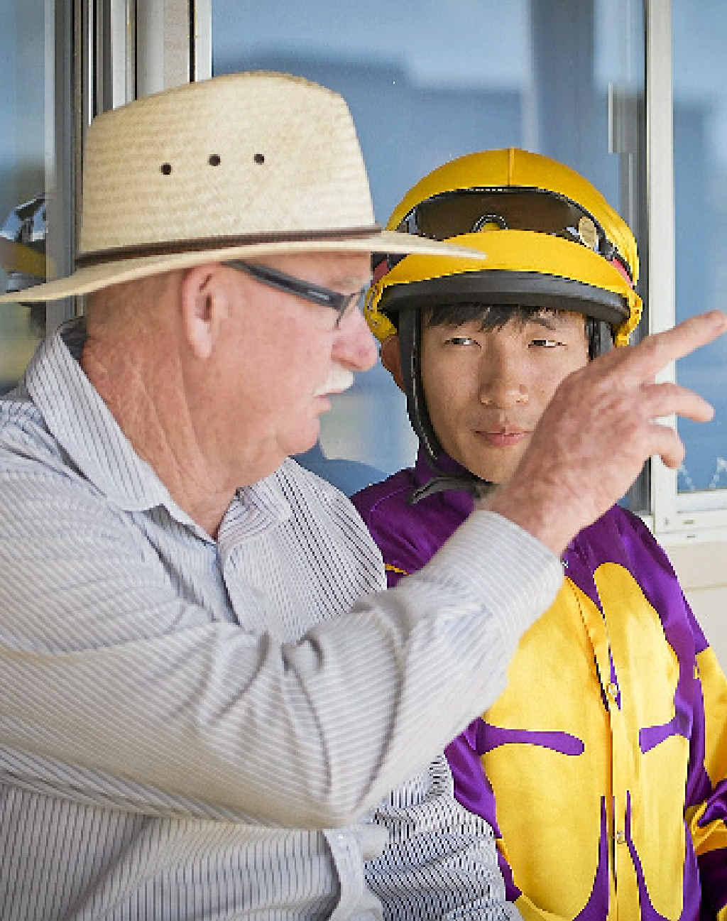 Trainer Lee Kiernan briefs Jockey Shenny Chan on his next race.