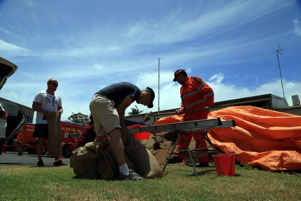 SES member Corey Waynwright (right) filling sandbags for concerned residents in Hervey Bay.