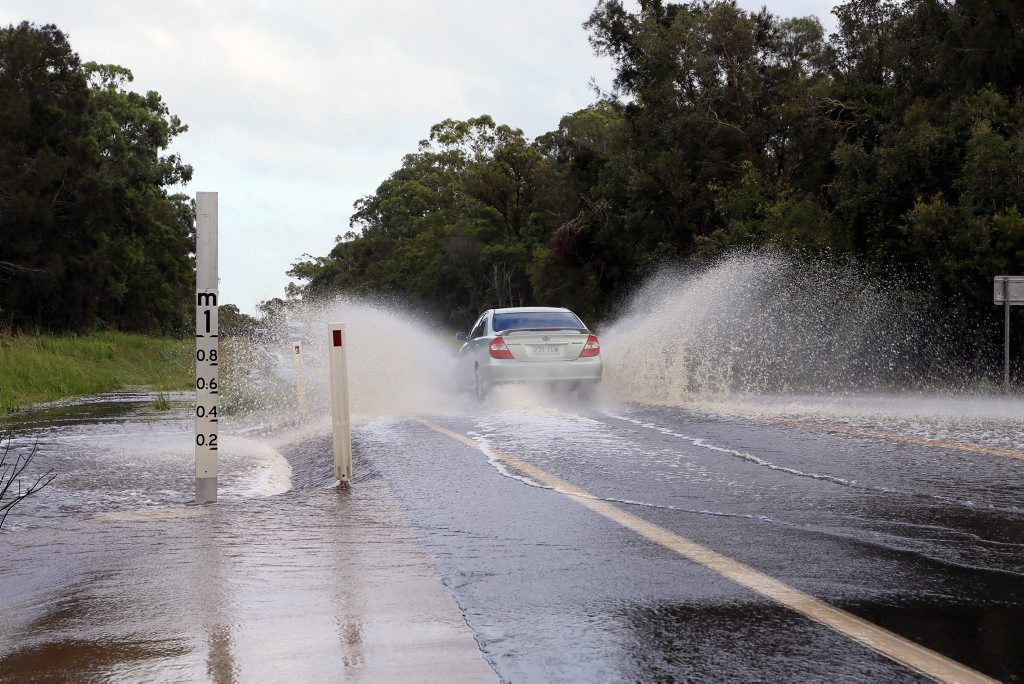 Motorists are driving through water across Booral Rd near the Main St intersection on Friday morning.
