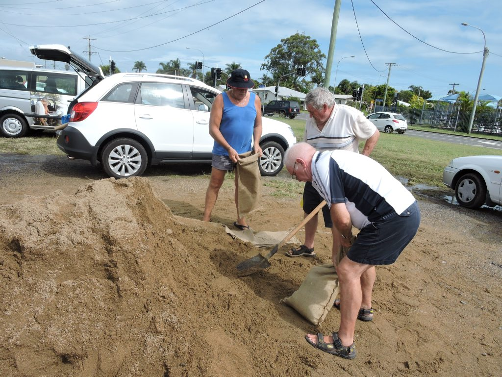 Lionel Buxton, John O'Sullivan and Ken Leynolds filling sandbags on Old Maryborough Rd hours before Cyclone Marcia impacts the Fraser Coast.