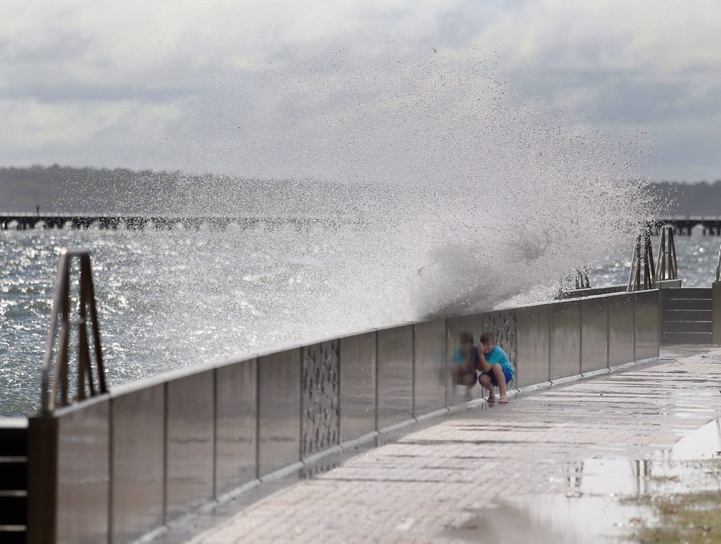 Nathaniel Fuller, a local 12 year old, ducking for cover as the king tide batters the Urangan seawall on Friday.