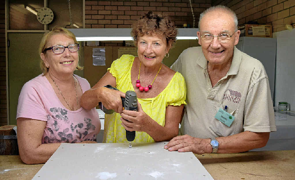 TRADING UP: Rita Davies, and Norm Thursby of the Buderim Men's Shed, look on as Laureen Delaney learns to drill a hole during the women's maintenance workshop at the shed.