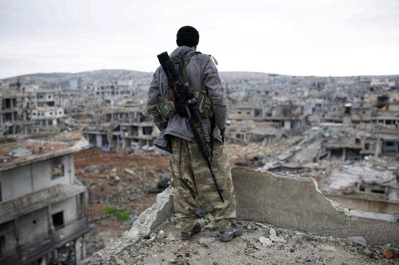 A Syrian Kurdish sniper looks at the rubble in the Syrian city of Ain al-Arab, also known as Kobani.