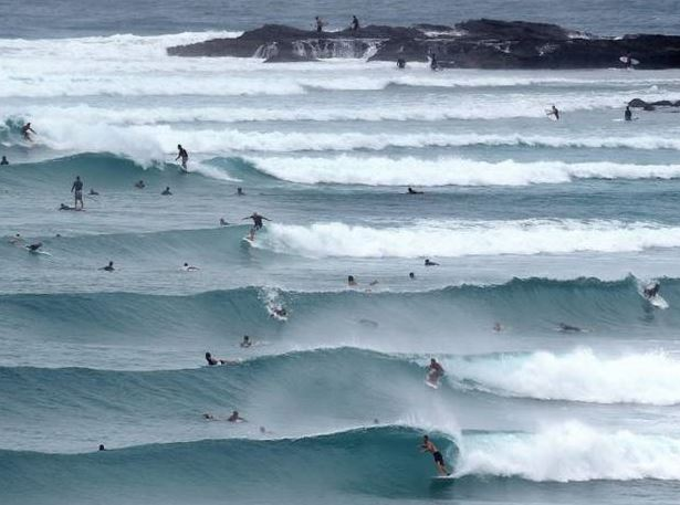 Risk-taking surfers hit the waves before TC Marcia hit the coast.