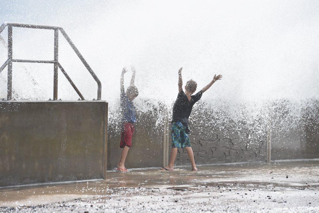 Storm surge at high tide - Seth,6, and Elijah,9, Cattell make the most of the waves crashing over the seawall at Urangan.