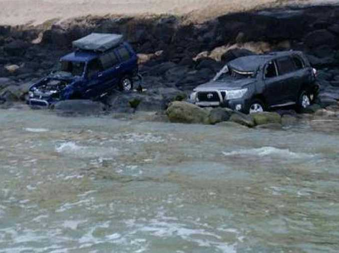CAUGHT OUT: A Holden Jackaroo and Toyota Landcruiser were pummelled by the high tide at Rainbow Beach's Mudlo Rocks on Sunday night.