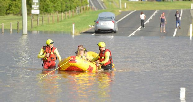RESCUE: Two young girls are rafted to dry ground by a swift water rescue crew after the car they were travelling in was driven into floodwater on Power Rd and stalled.