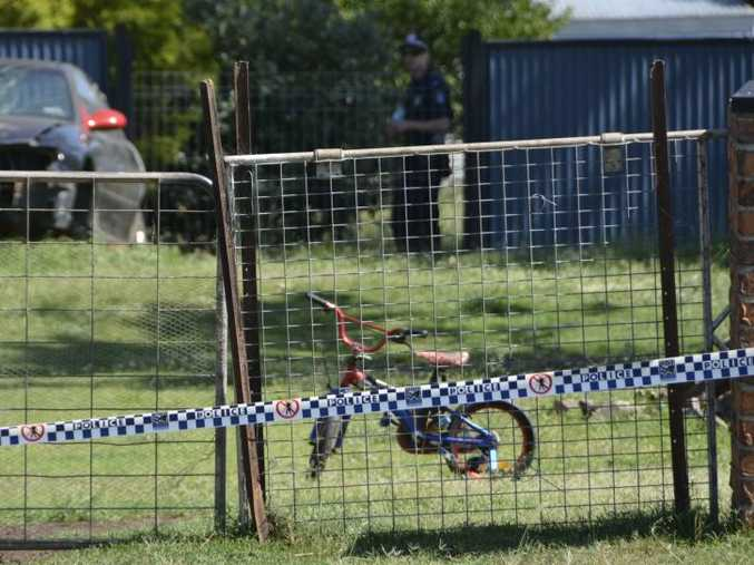 A child's pushbike sits in the yard of a Biddeston home where a man, woman and child were found dead on March 2, 2015.