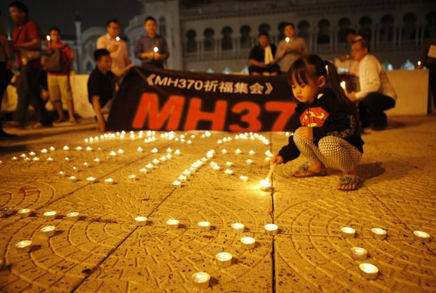 People light up candles and hold a banner during a candlelight vigil for the passengers aboard the missing Boeing 777-200 plane of Malaysia Airlines Flight MH370 in Kuala Lumpur, Malaysia, 10 March 2014.