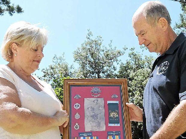 LEGACY: Sawtell's Linda Jones presents family Anzac memorabilia to Sawtell RSL Sub-branch president Dallas Burrage for next month's Anzac Day service.