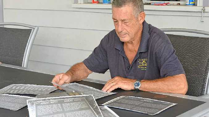 Eric Winn looks over photographs of the original plaques placed at Gallipoli.