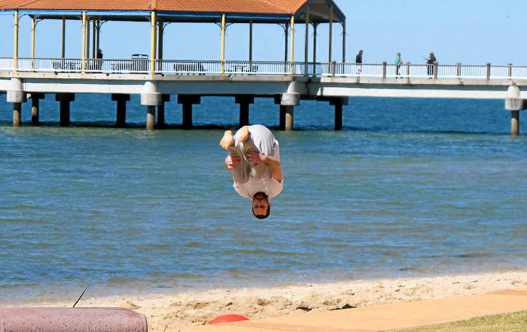 David Stuart performs a front somersault after bouncing off a semi-buried fitness ball on the beach.