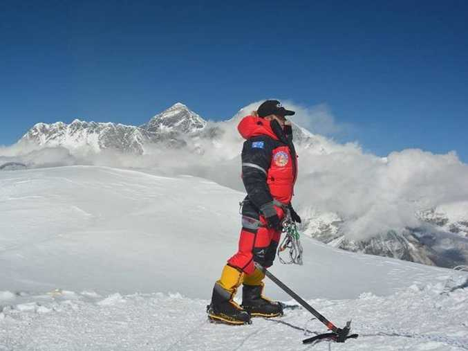 Alyssa Azar on the summit of Ama Dablam with Mount Everest rising in the background behind her.